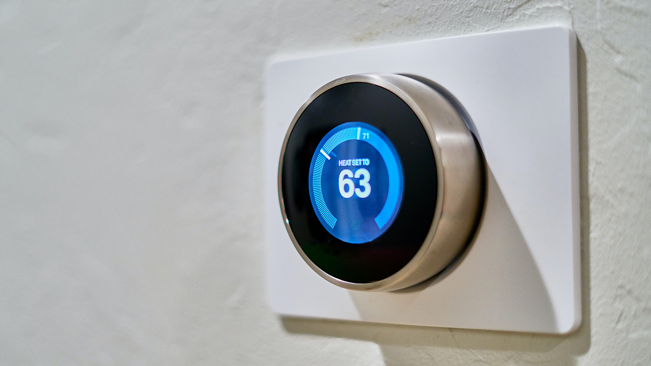 A smart thermostat mounted on a wall.